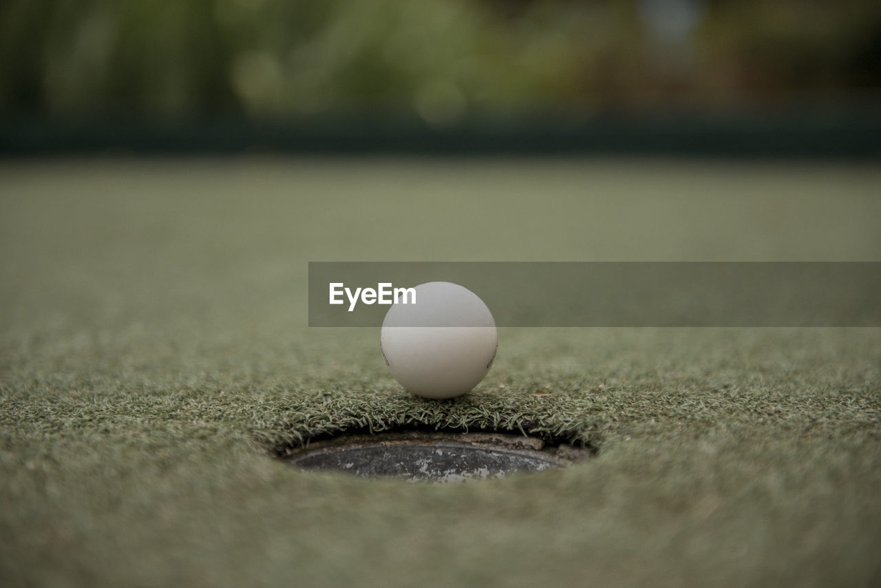 Close-Up Of Golf Ball By Hole On Court
