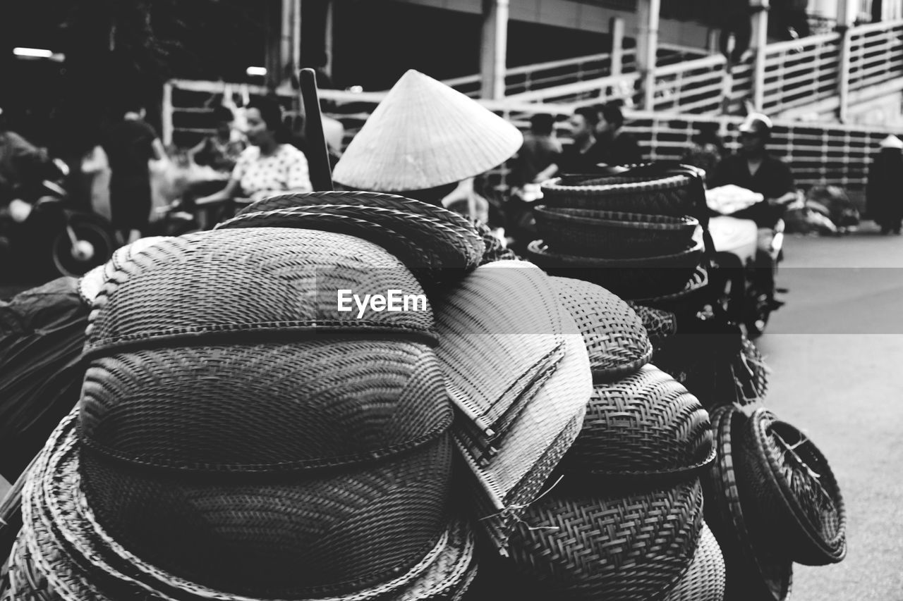 transportation, day, mode of transportation, focus on foreground, rear view, hat, large group of objects, close-up, stack, outdoors, land vehicle, real people, men, abundance, street, city, headwear, motorcycle, still life, wheel
