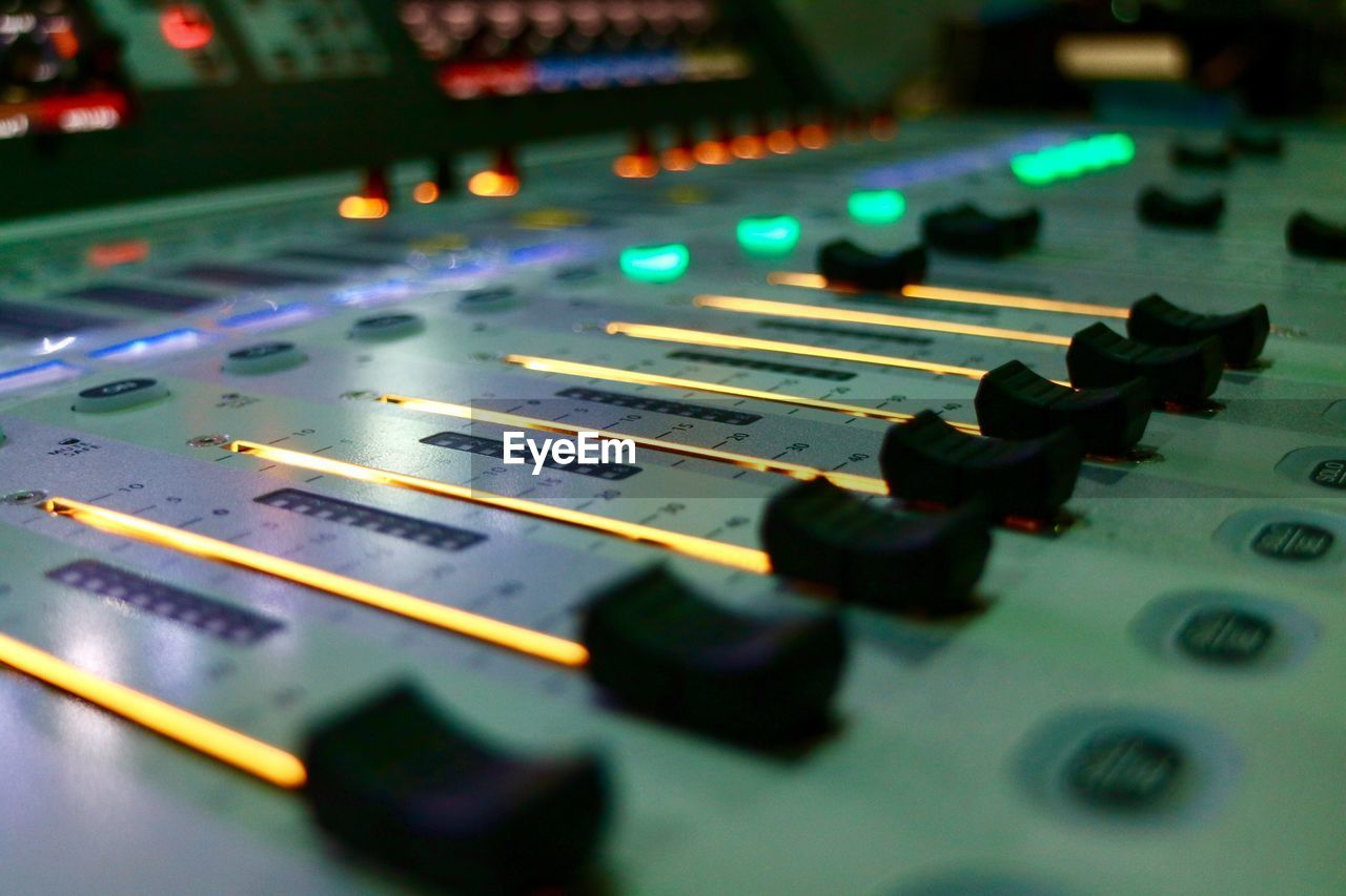 close-up, selective focus, indoors, music, arts culture and entertainment, no people, control, audio equipment, technology, sound recording equipment, sound mixer, illuminated, high angle view, control panel, pattern, musical instrument, still life, equipment, studio, table, push button, nightlife