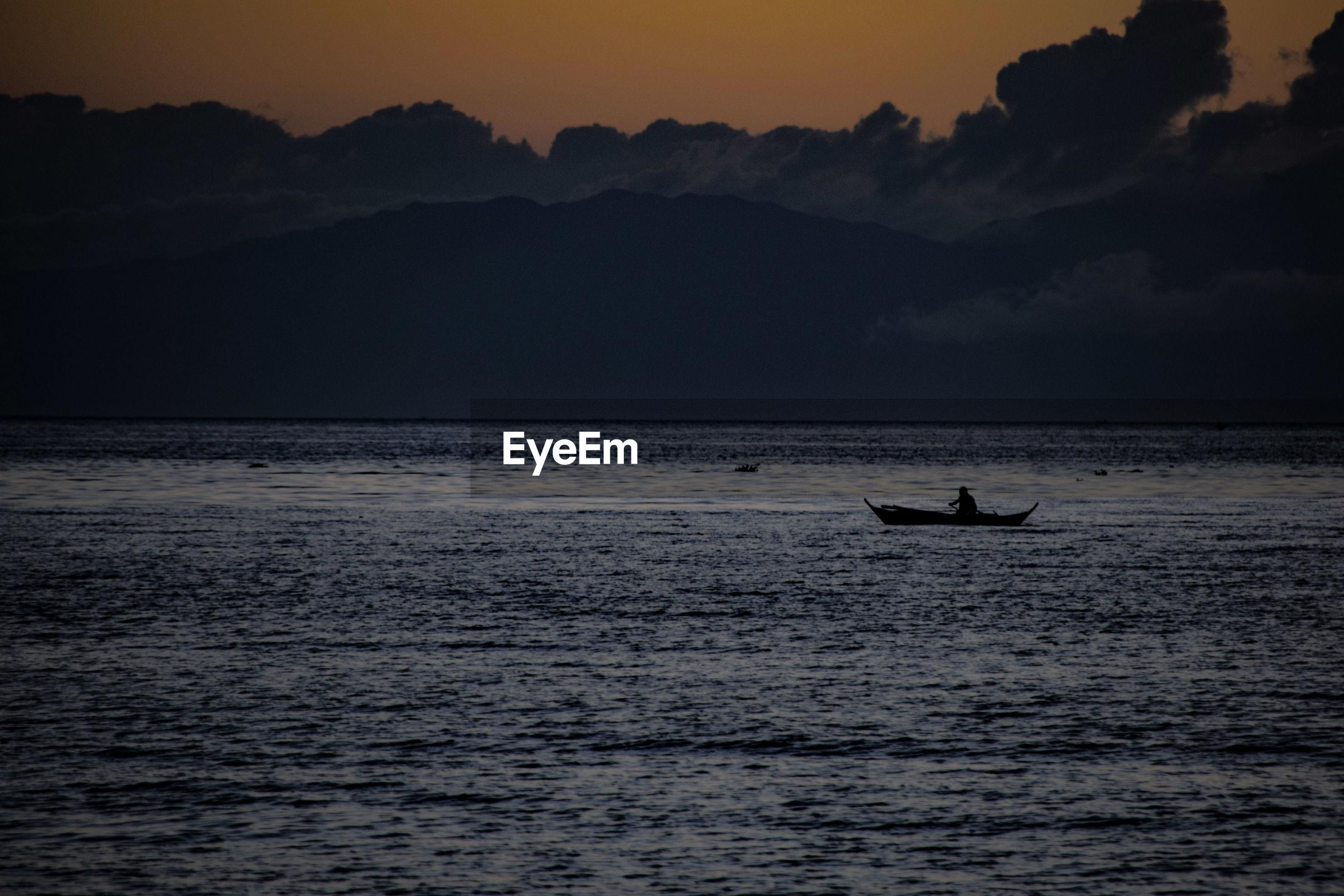 Silhouette on sea against sunset sky
