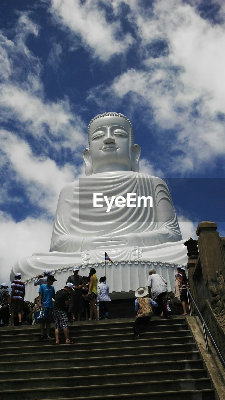 Low angle view of white buddha statue against sky