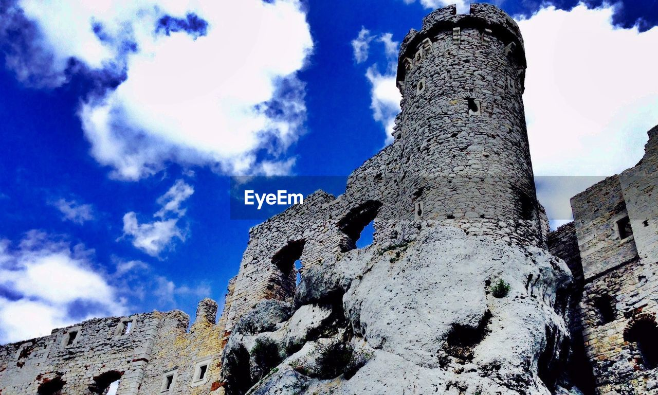 Low angle view of old ruin castle against blue sky