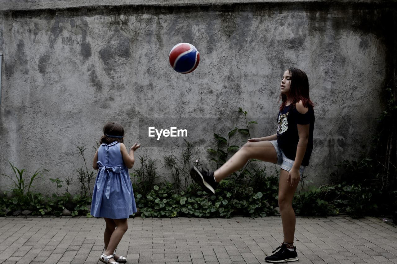 Sisters playing with ball while standing on footpath against wall