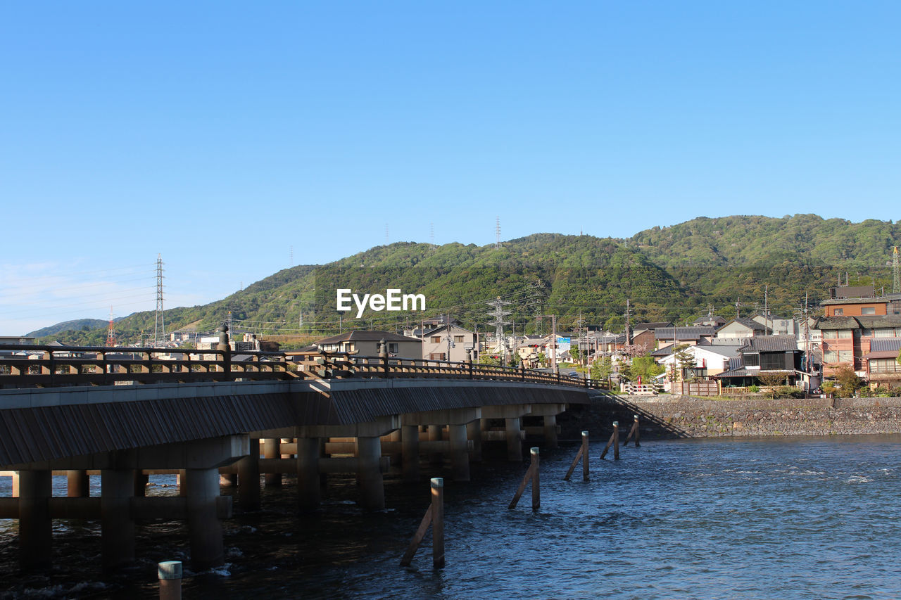 architecture, built structure, water, building exterior, clear sky, river, connection, blue, town, day, bridge - man made structure, waterfront, outdoors, no people, nature, tree, sky