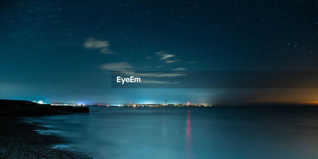 SCENIC VIEW OF SEA AGAINST STAR FIELD IN SKY AT NIGHT