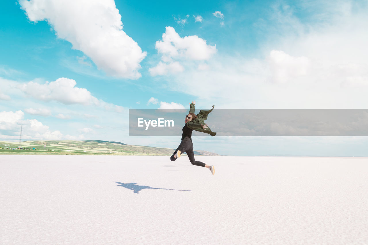 Full Length Rear View Of Woman Jumping At Beach During Sunny Day