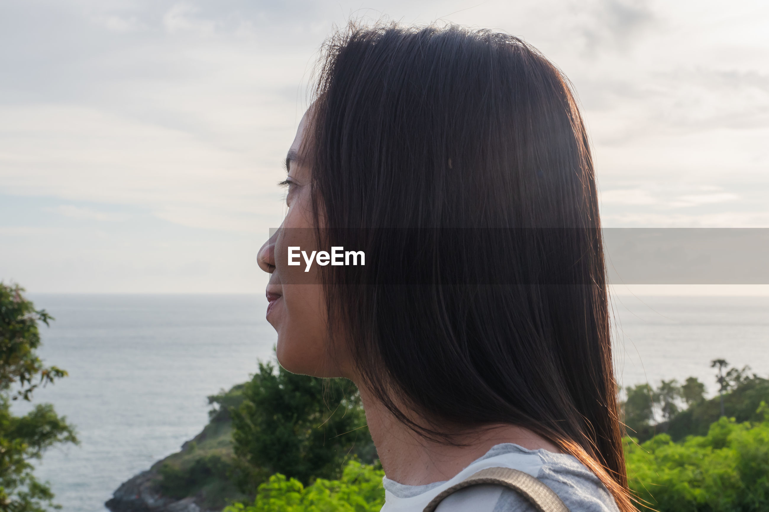 PORTRAIT OF YOUNG WOMAN LOOKING AT SEA