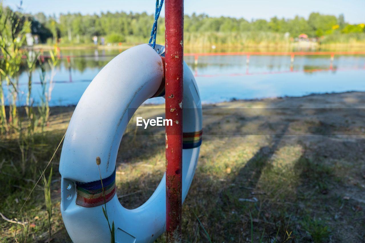 Lifebelt on metal pole on shore