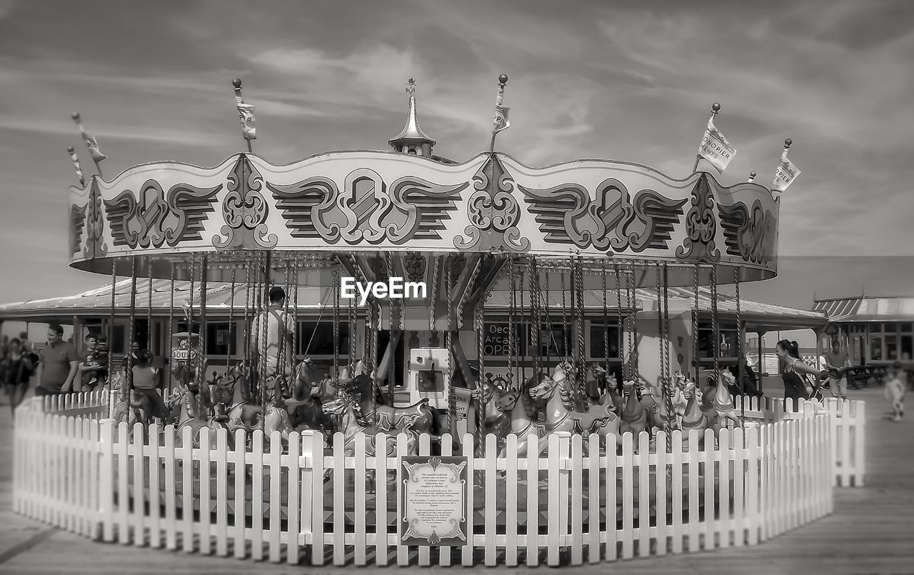 amusement park, arts culture and entertainment, amusement park ride, sky, built structure, carousel, cloud - sky, outdoors, architecture, day, merry-go-round, building exterior, no people