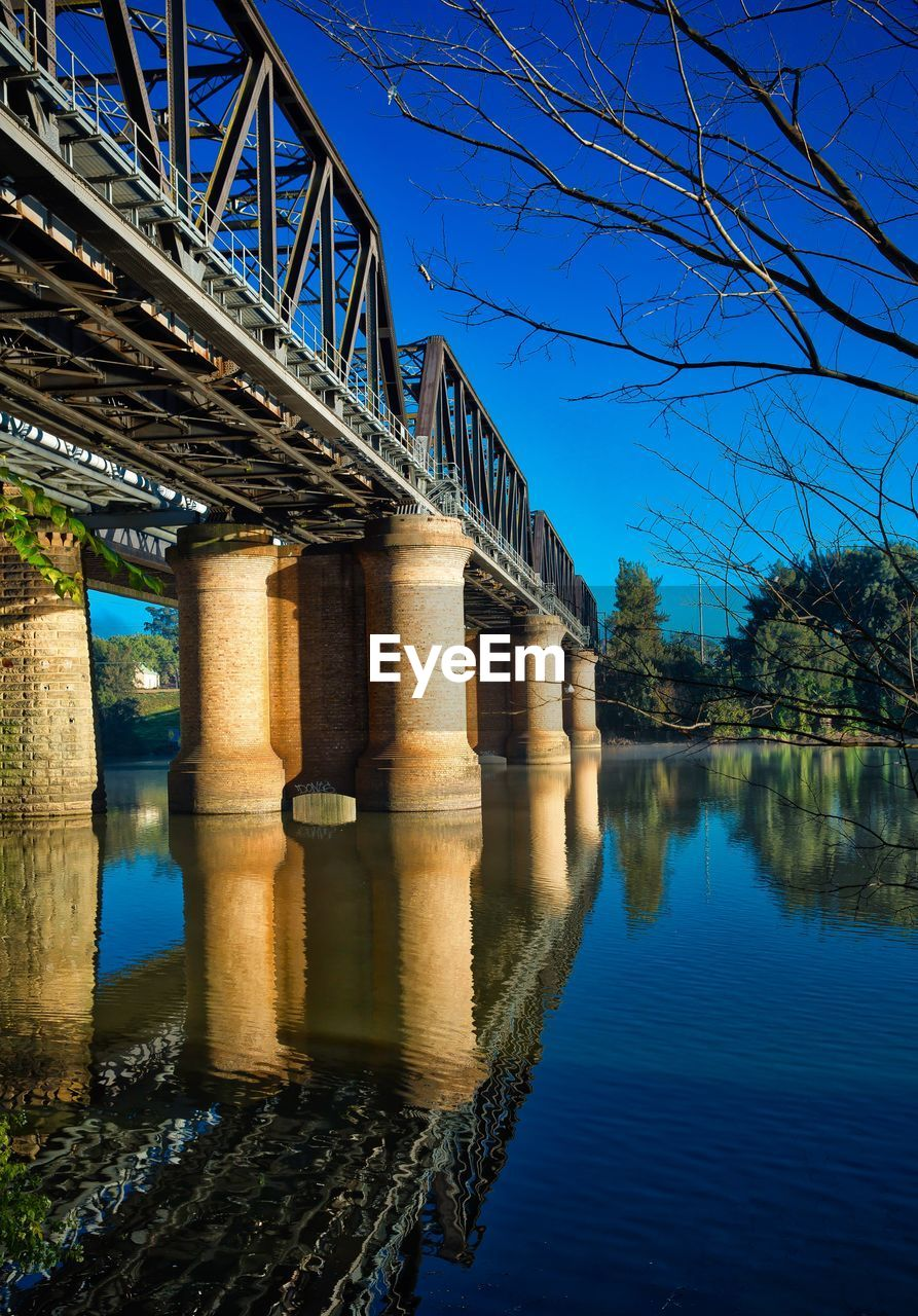 bridge - man made structure, connection, architecture, engineering, water, built structure, river, below, underneath, architectural column, outdoors, reflection, bridge, waterfront, blue, day, low angle view, nature, no people, clear sky, sky, tree
