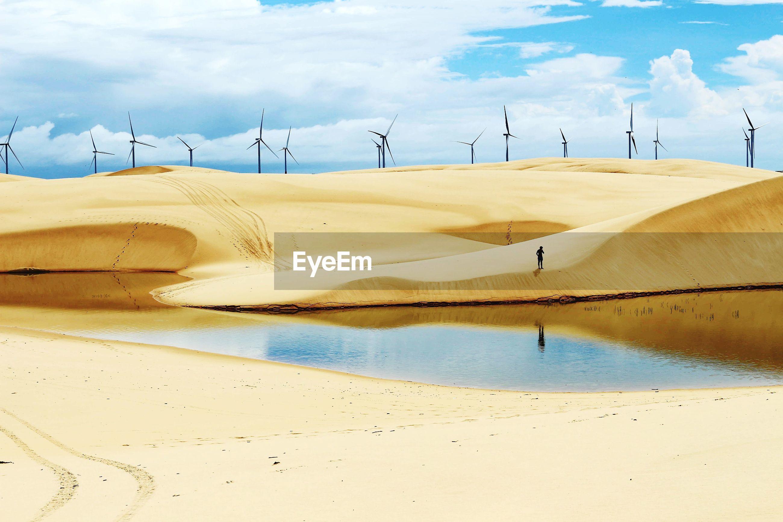 Windmills on sand at beach against cloudy sky