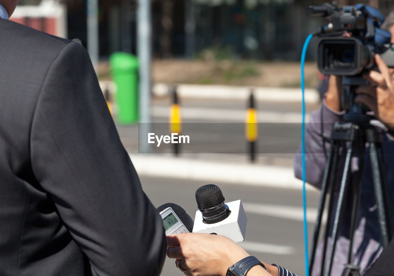 Cropped hand of person holding microphone on the front of man with camera in background