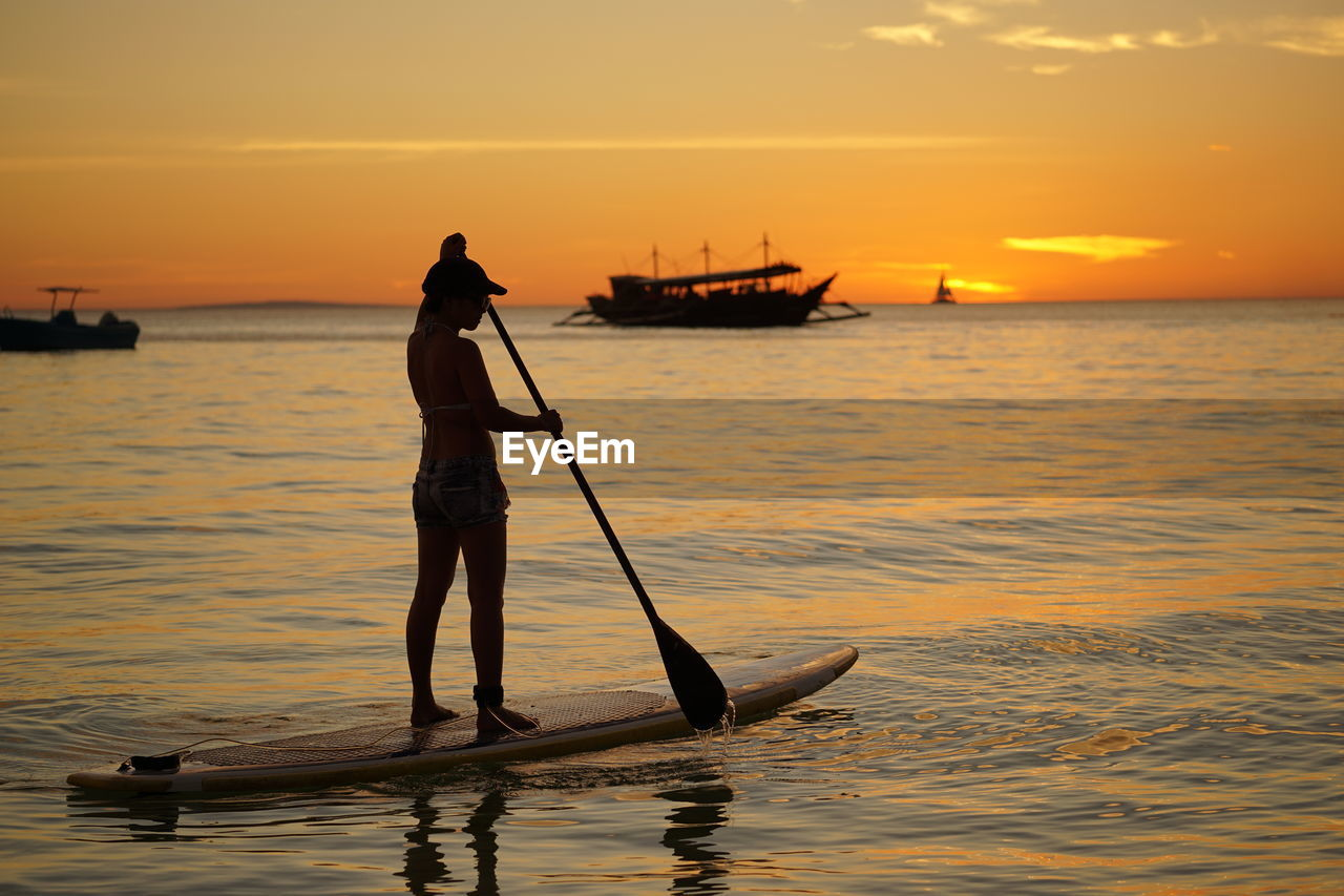 Silhouette woman paddleboarding in sea against orange sky