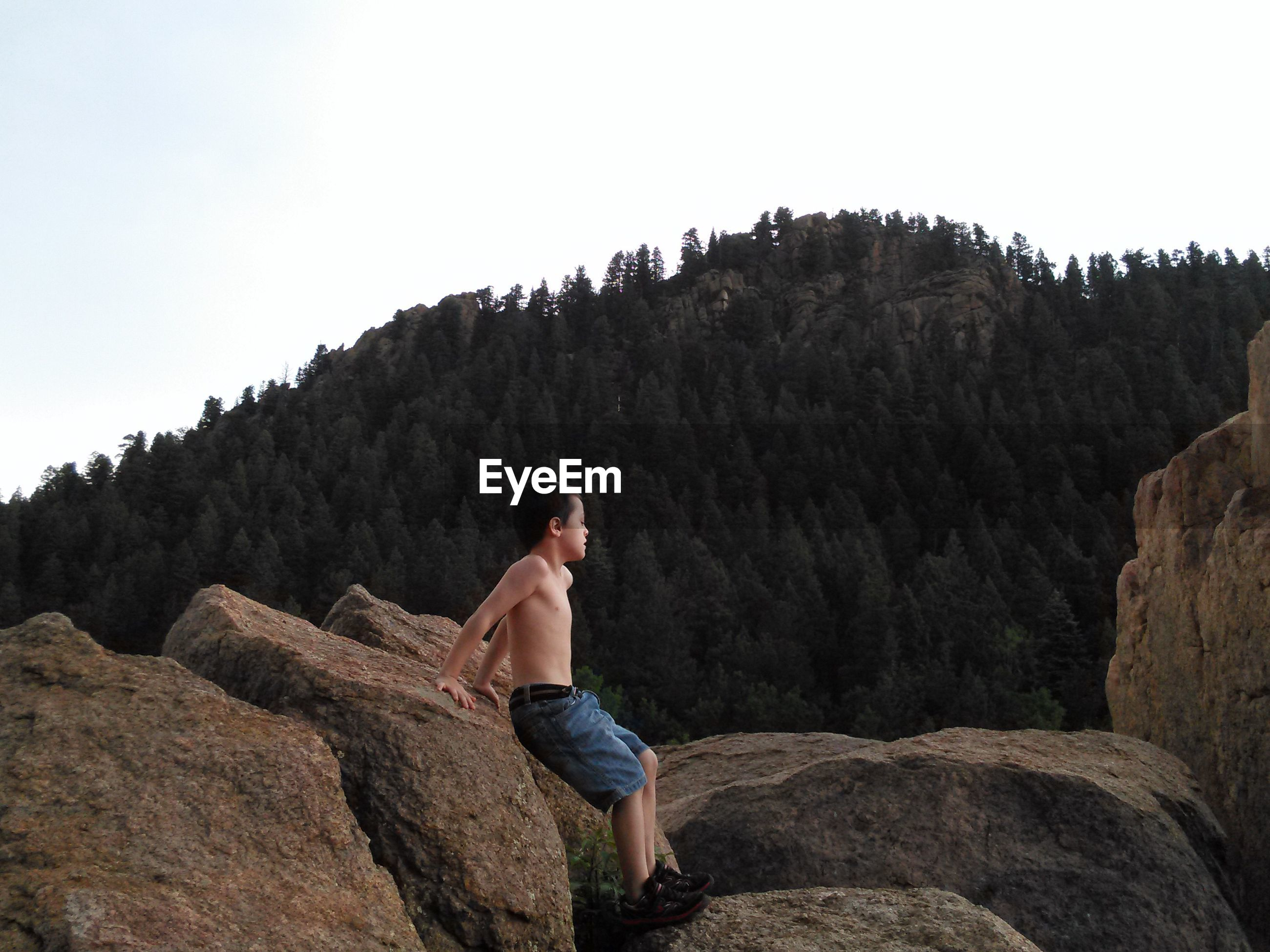Full length of shirtless boy leaning on rock against mountain