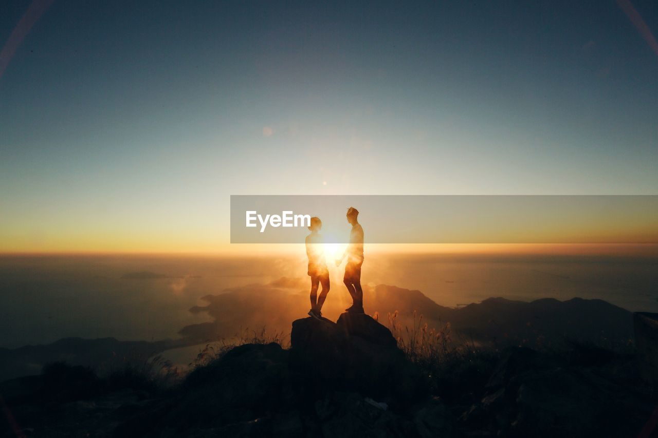 Silhouette Couple Standing On Rock Formation Against Sky During Sunset