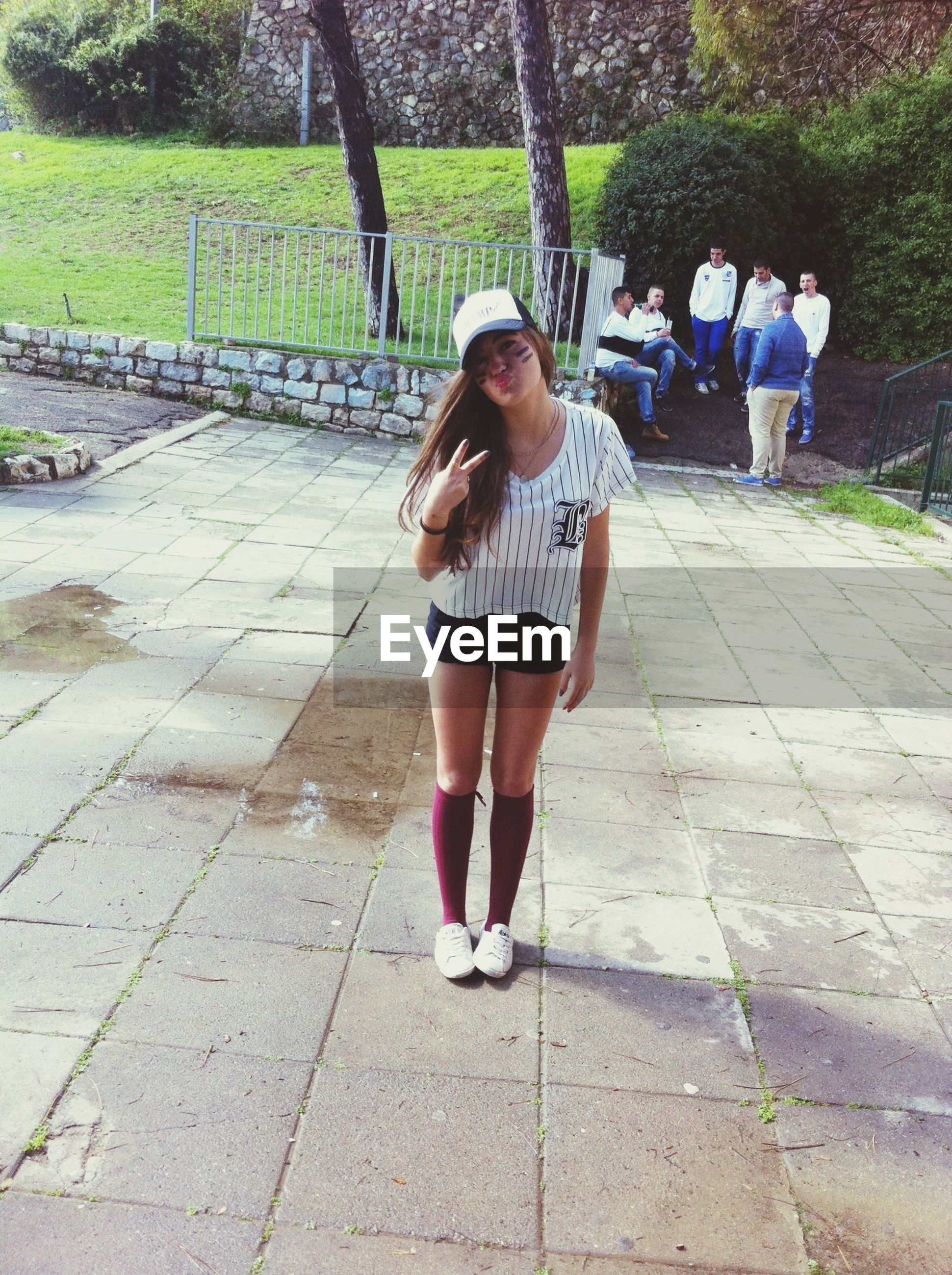 full length, casual clothing, lifestyles, leisure activity, person, girls, standing, childhood, young women, elementary age, front view, footpath, park - man made space, young adult, sunlight, long hair, walking, looking at camera