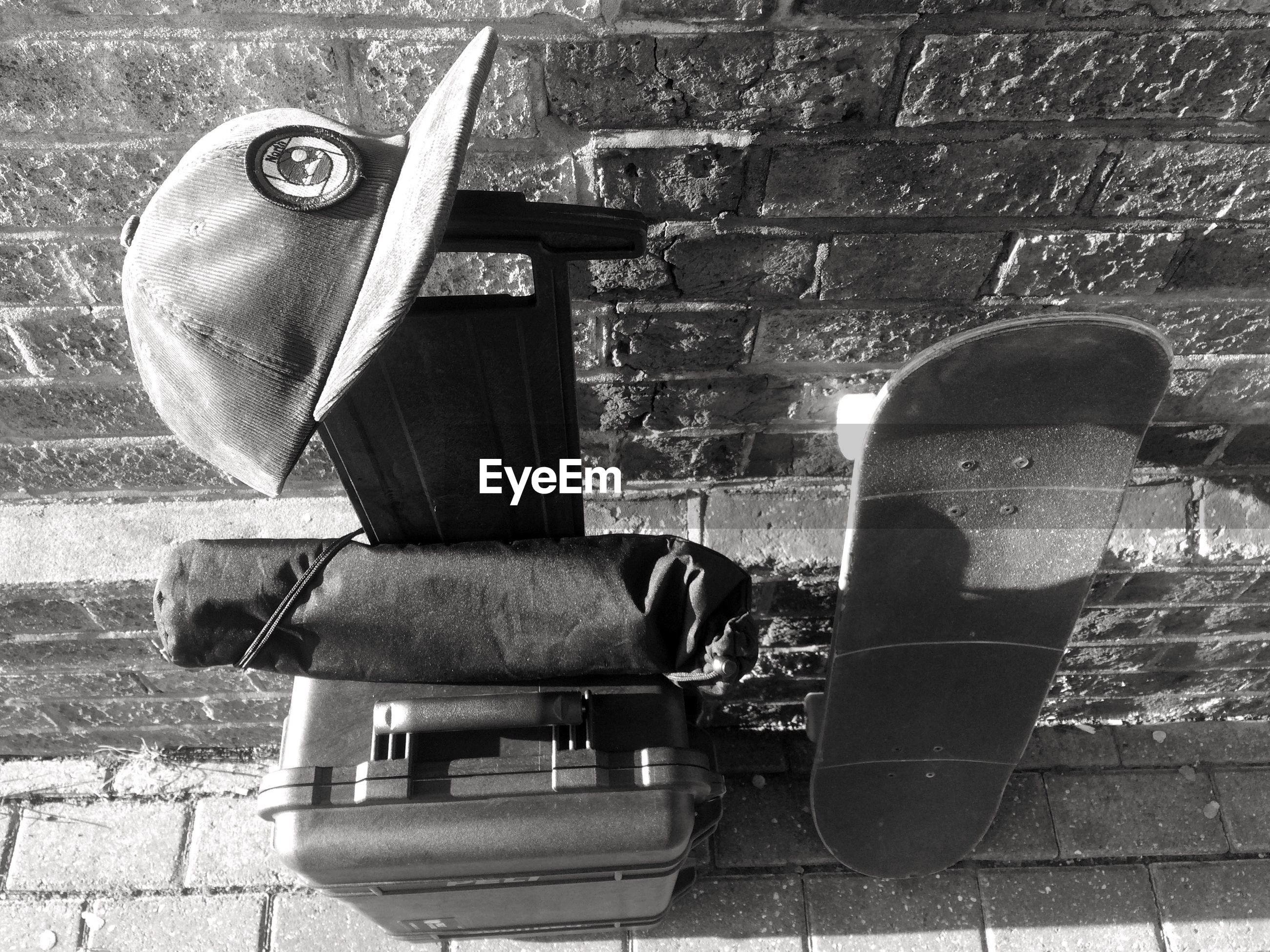 High angle view of skateboard and bag against wall