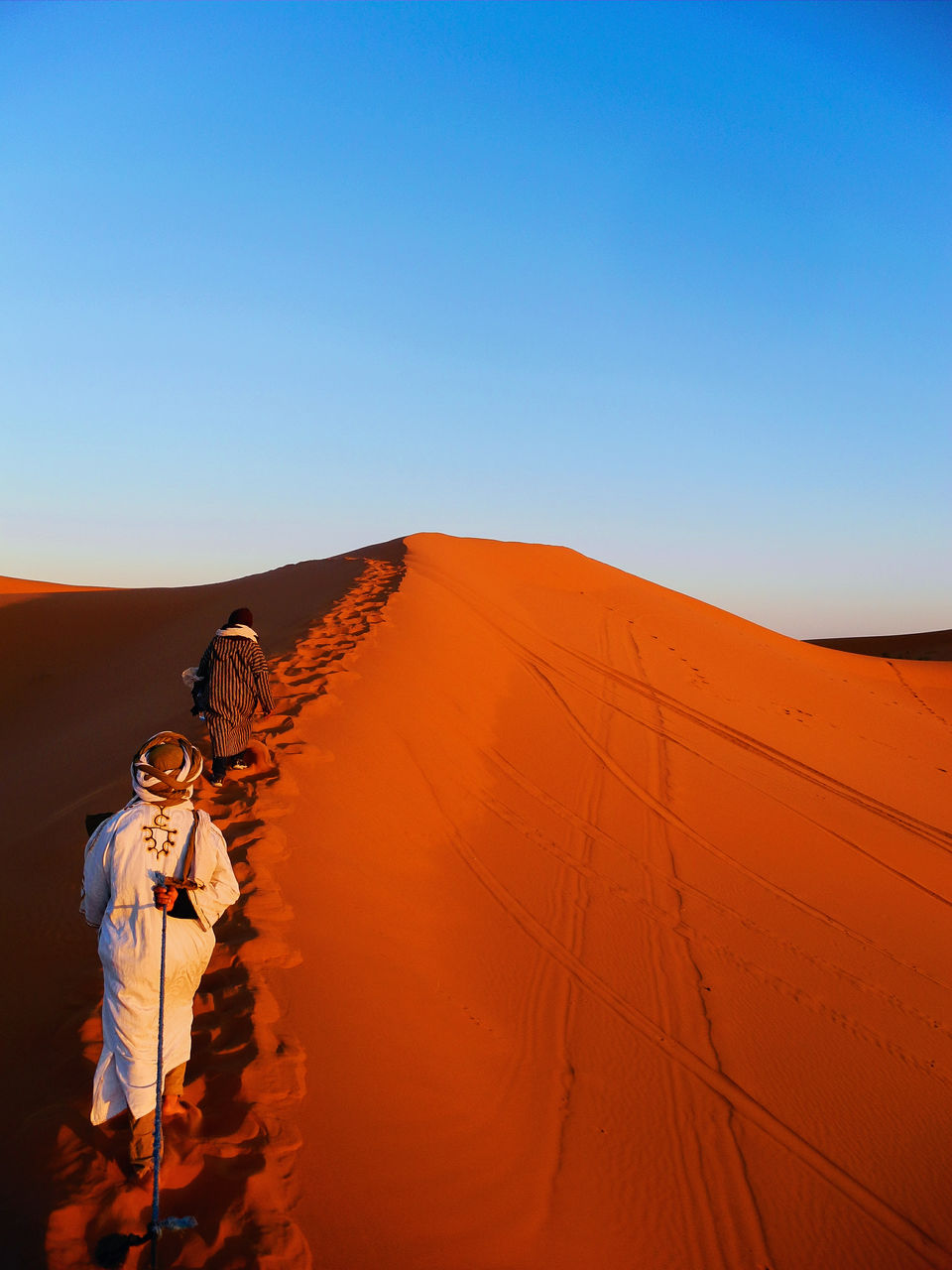 Rear View Of People Walking On Sand Dune Against Clear Blue Sky