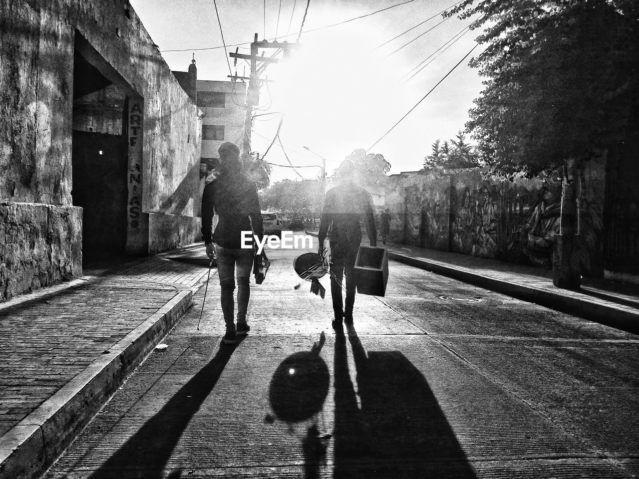 real people, full length, architecture, men, transportation, shadow, nature, sunlight, two people, built structure, walking, building exterior, city, day, rear view, lifestyles, people, footpath, tree, street, outdoors