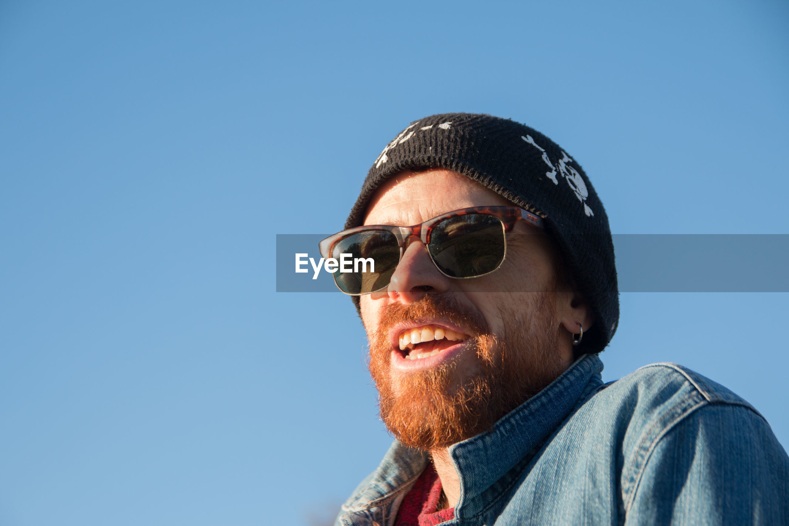 PORTRAIT OF MAN WEARING SUNGLASSES AGAINST BLUE SKY