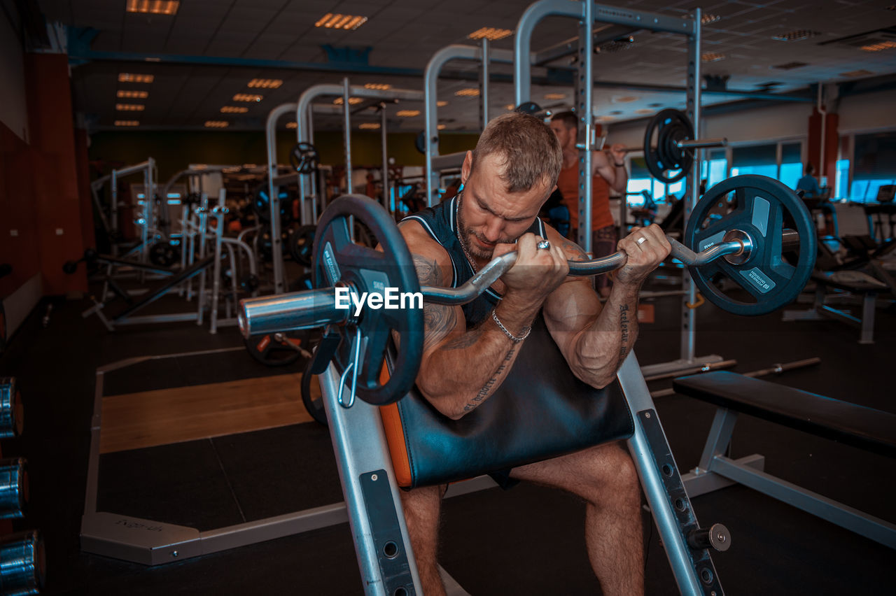 muscular build, exercising, sports training, strength, gym, one person, sport, healthy lifestyle, weight training, wellbeing, weight, exercise equipment, lifestyles, indoors, health club, men, real people, vitality, adult, front view, equipment, effort, mature men, bicep, physical activity, exercise machine, body conscious