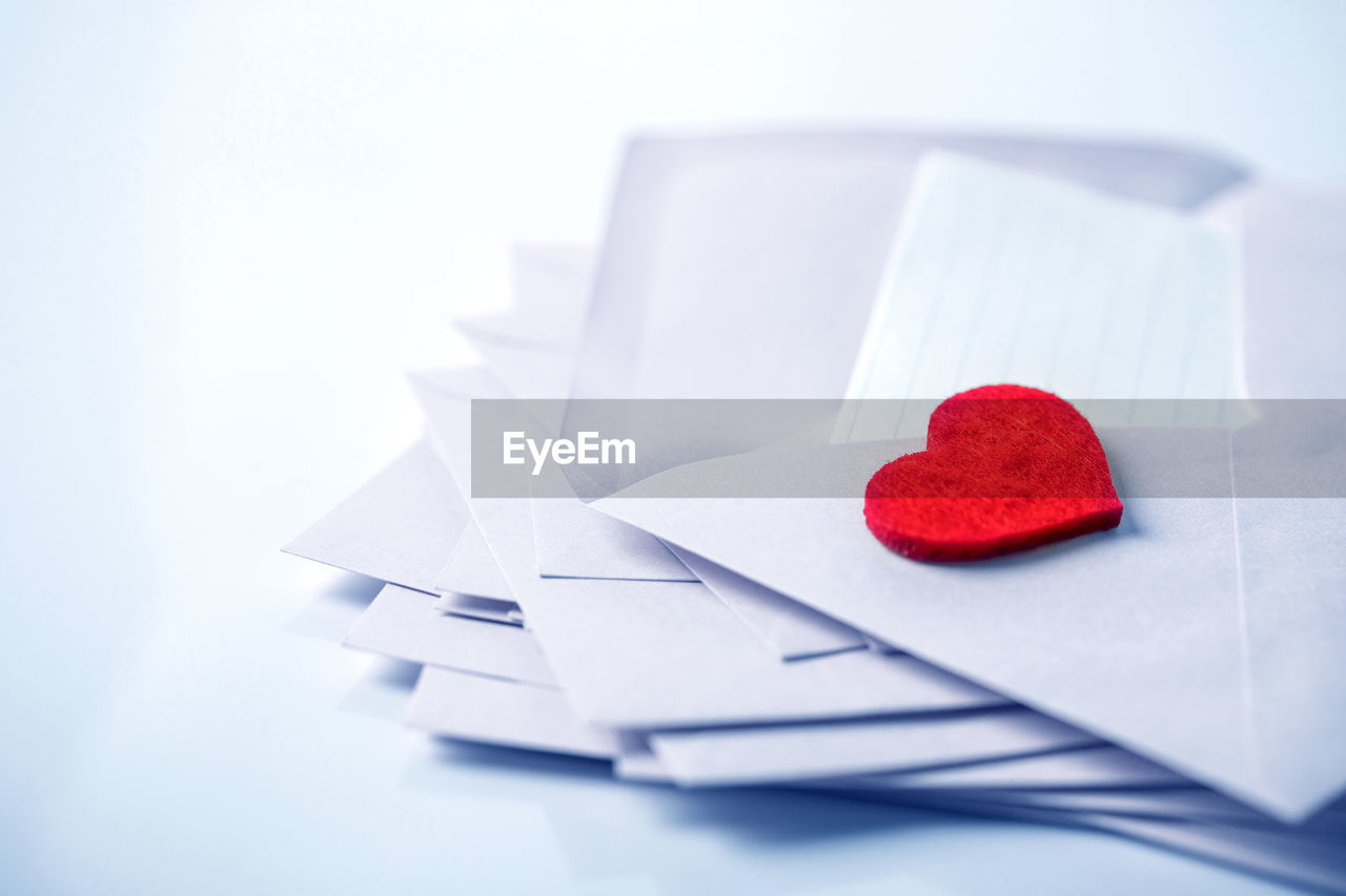 Close-Up Of Red Heart Shape On Envelope Over White Background
