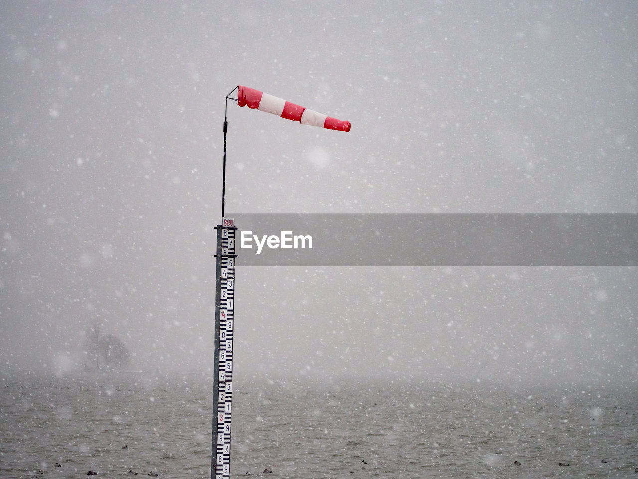 water, day, nature, fog, no people, cold temperature, winter, metal, sky, lighting equipment, red, beauty in nature, outdoors, sea, waterfront, beach, pole, snow