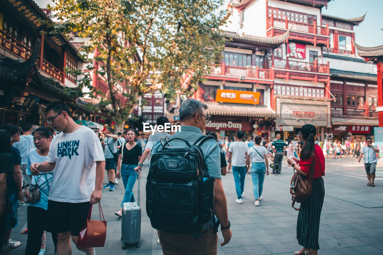 architecture, real people, building exterior, city, built structure, group of people, large group of people, crowd, men, adult, women, street, text, city life, casual clothing, building, day, script, walking