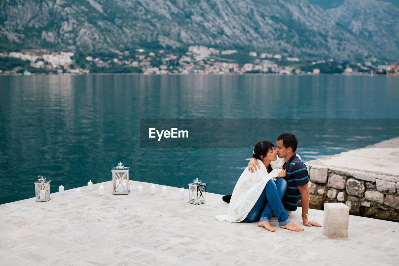 Couple Sitting On Lakeshore