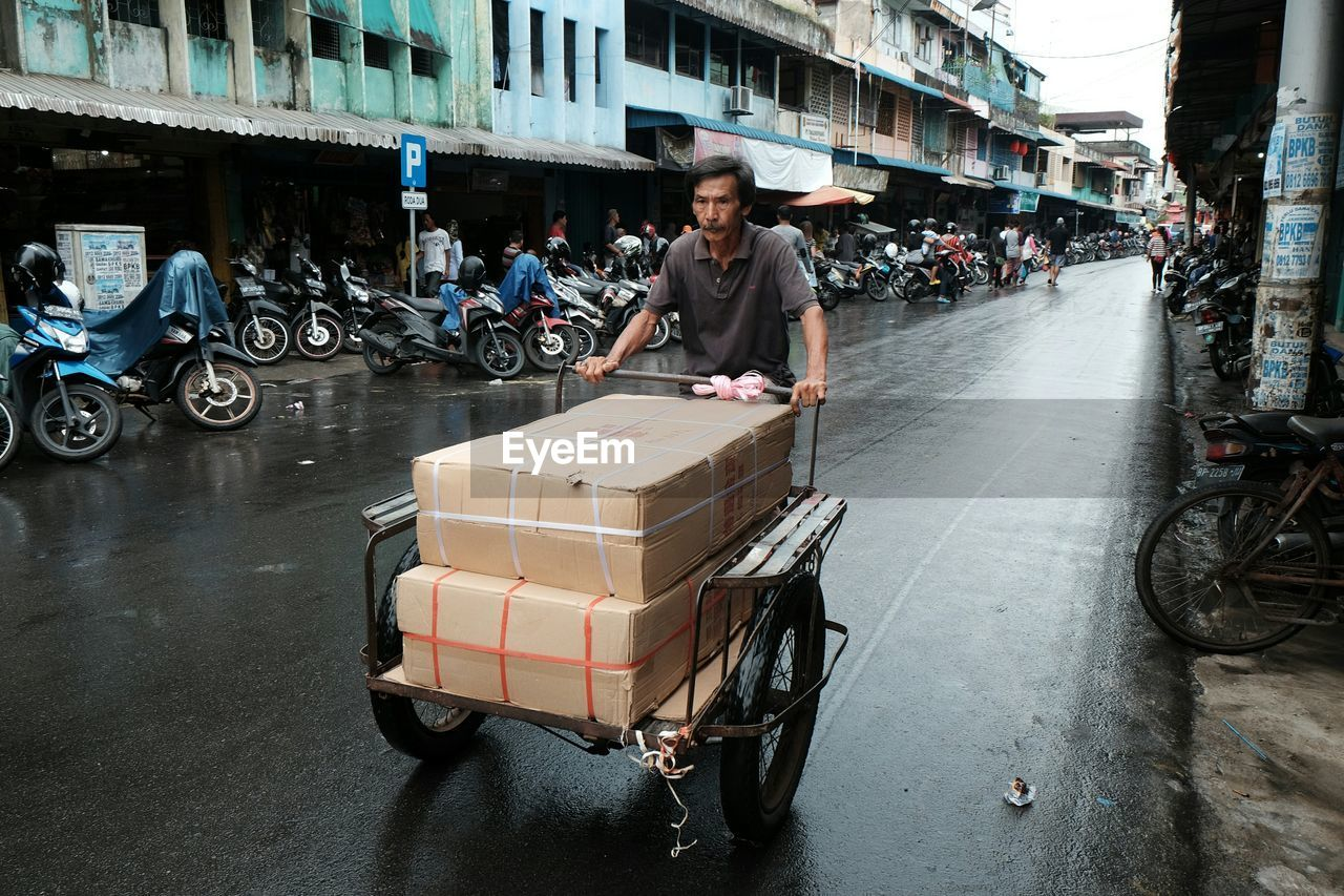 Close-up of mature man with boxes over push cart on road in city
