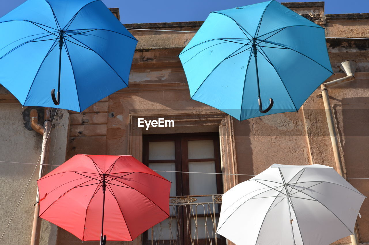 umbrella, protection, security, architecture, built structure, safety, building exterior, blue, day, rain, nature, low angle view, parasol, outdoors, no people, building, wet, city, clear sky