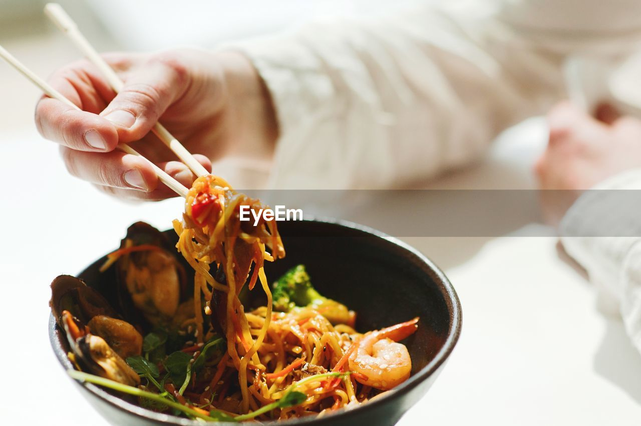 Midsection Of Person Holding Food In Restaurant