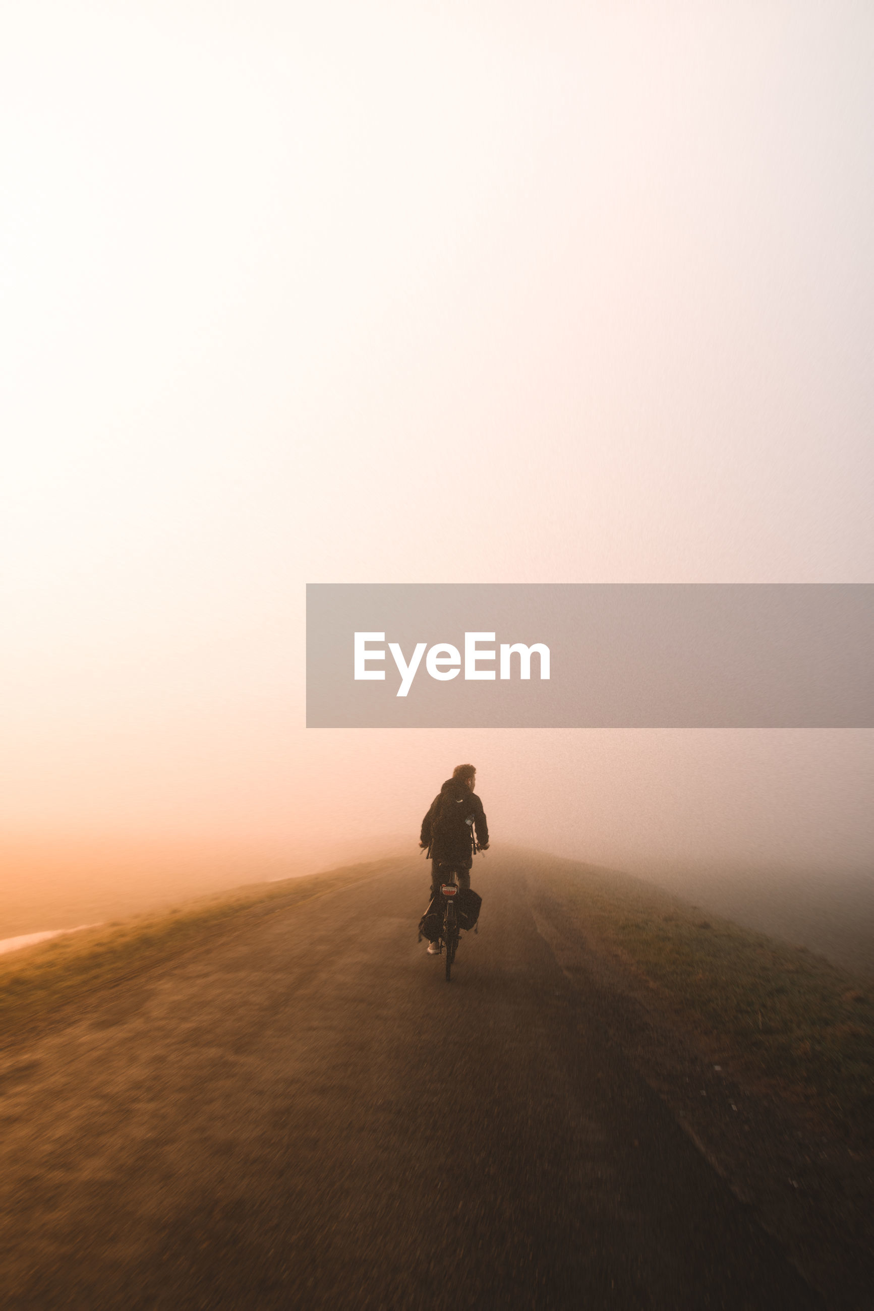 Rear view of man cycling on road during foggy weather