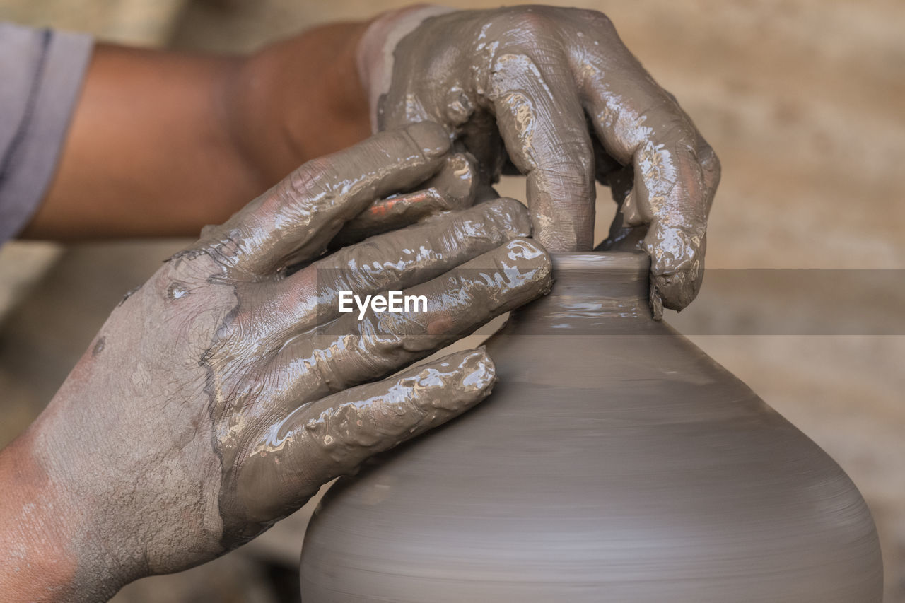 human hand, hand, human body part, working, real people, focus on foreground, one person, occupation, indoors, creativity, holding, art and craft, close-up, body part, men, dirt, molding a shape, craft, skill, finger, dirty
