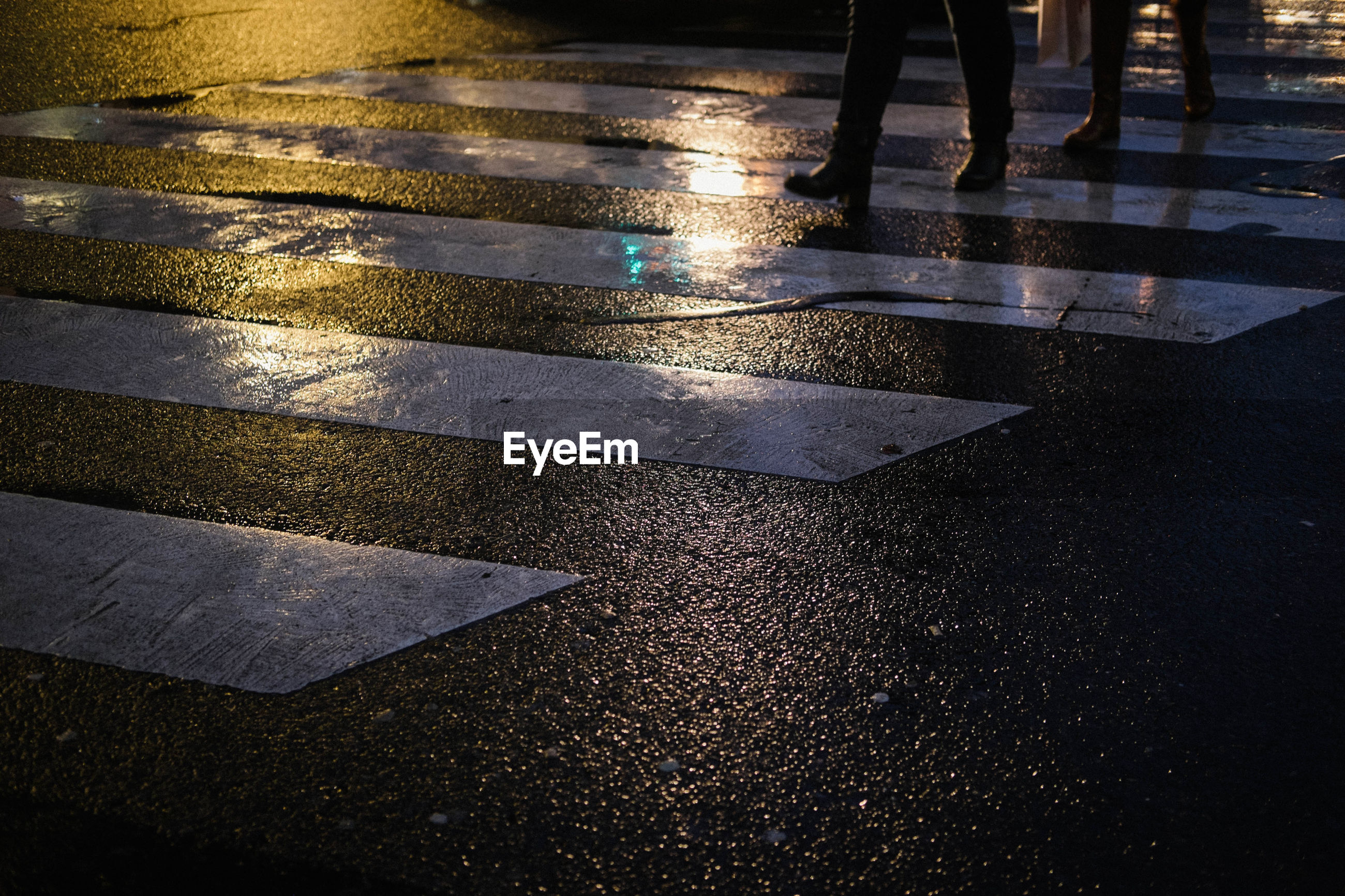 Low section of people walking on wet road at night
