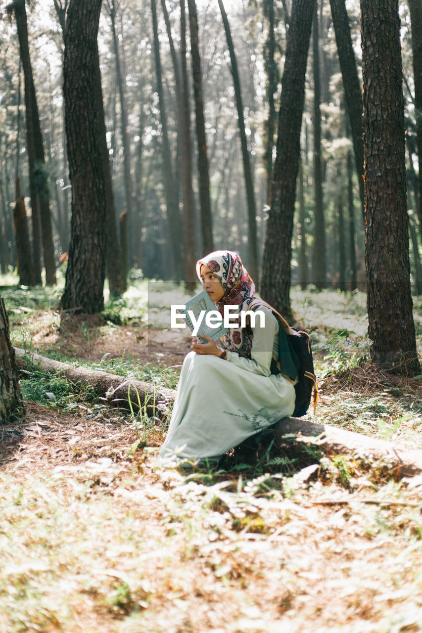 YOUNG WOMAN SITTING IN FOREST