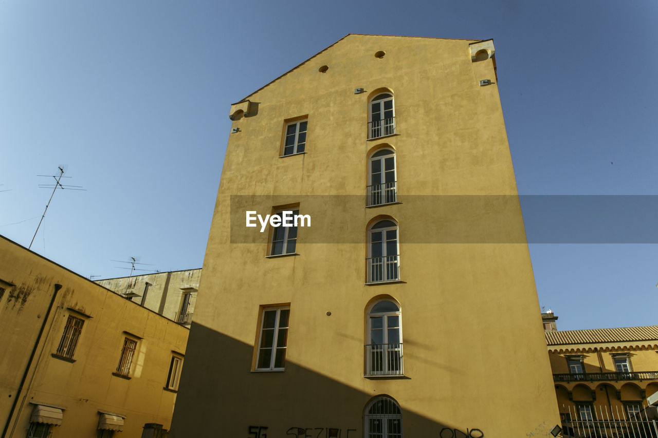 building exterior, architecture, built structure, low angle view, window, yellow, no people, clear sky, outdoors, day, residential building, sky, city