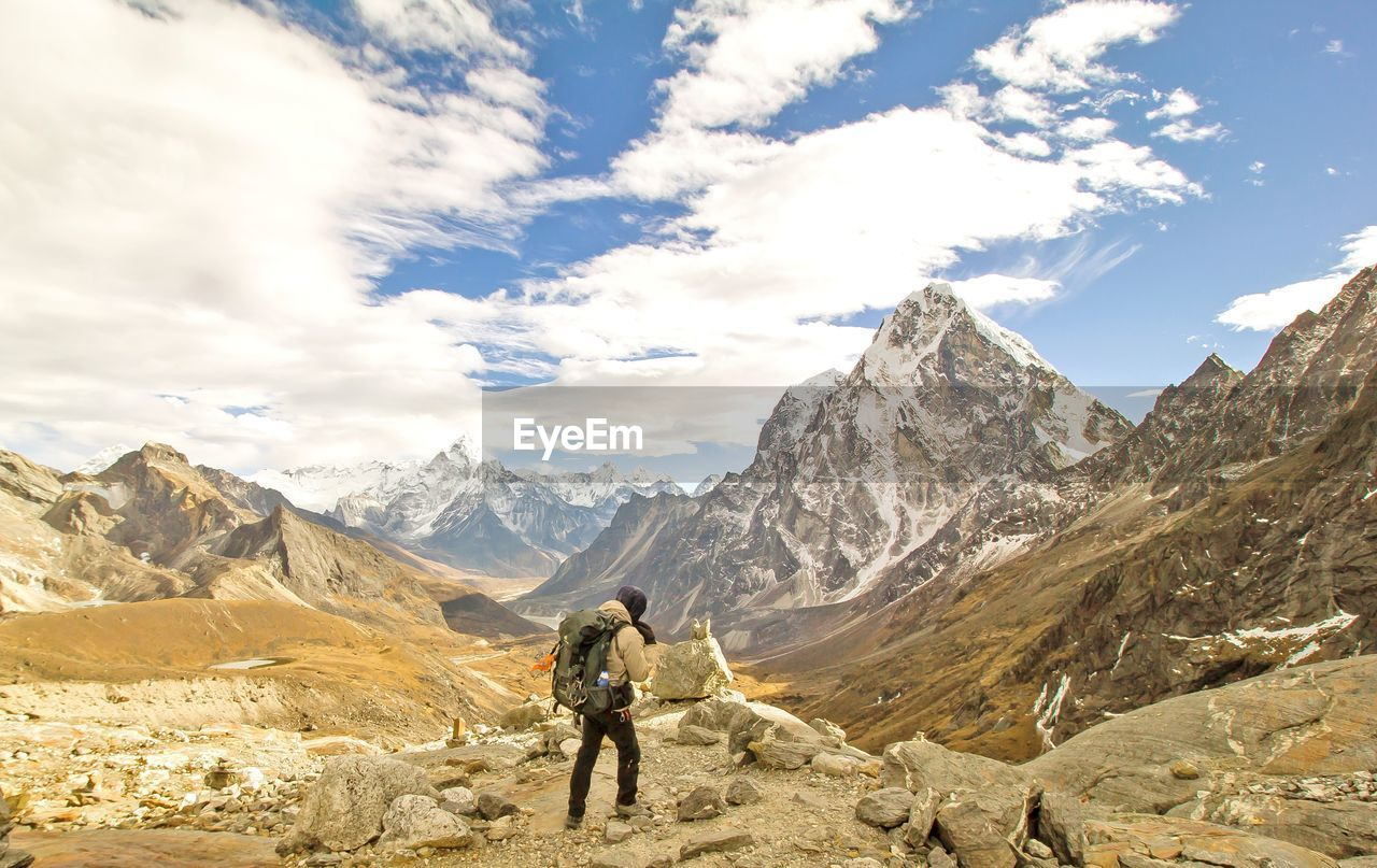 Rear view of backpacker walking on mountain against sky