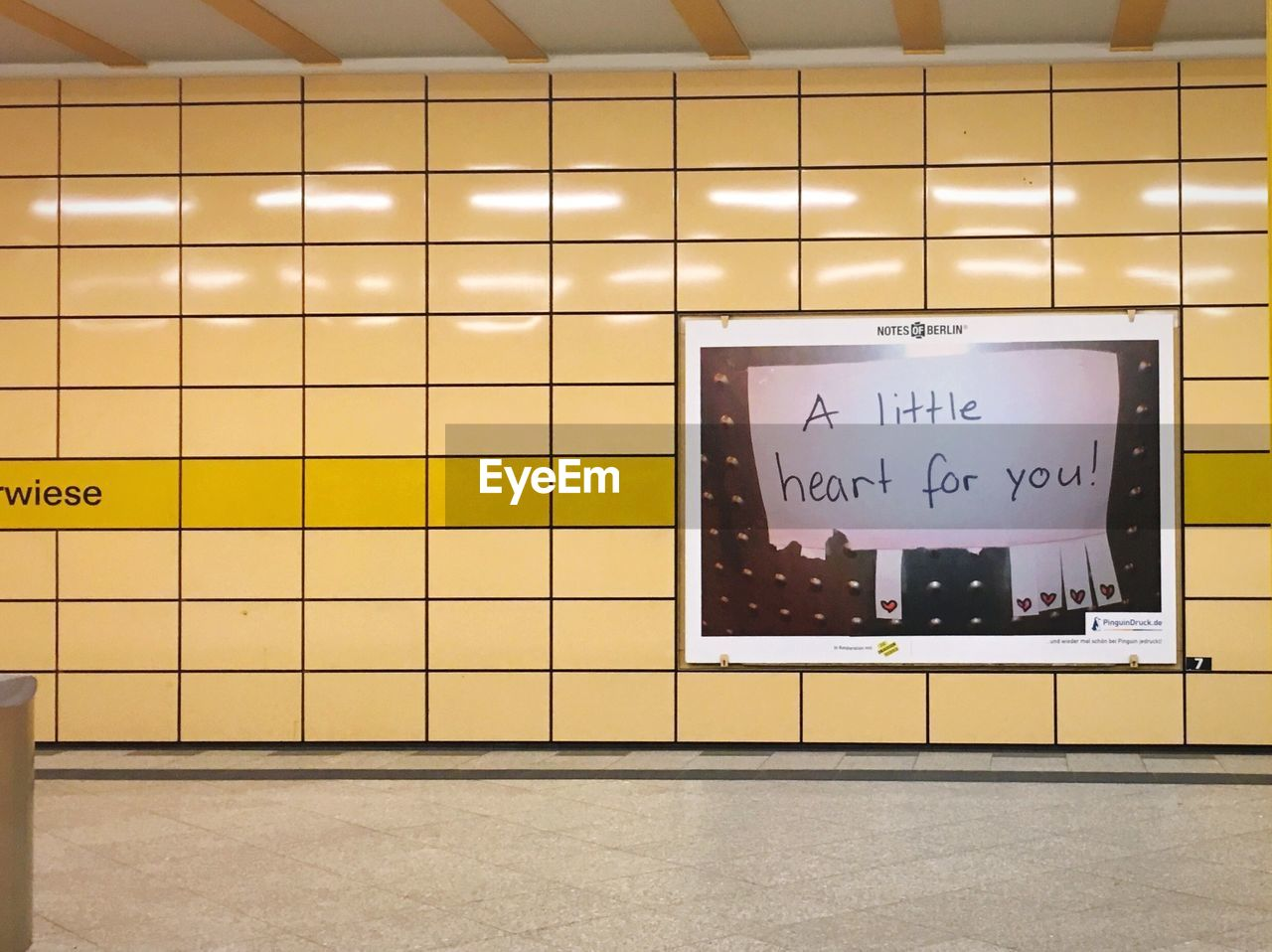 text, communication, indoors, wall - building feature, western script, tile, flooring, no people, illuminated, information, information sign, architecture, sign, yellow, lighting equipment, subway station, non-western script, script, built structure, arrow symbol, message