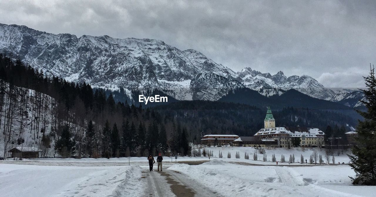 People walking on street against bavarian alps