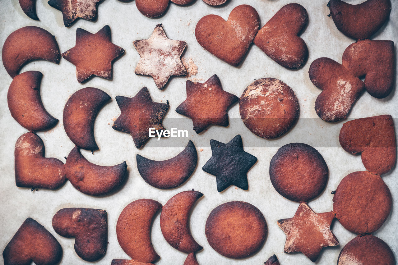 food, food and drink, freshness, indoors, sweet food, shape, design, close-up, no people, baked, cookie, still life, arrangement, large group of objects, full frame, indulgence, brown, heart shape, variation, temptation, order, gingerbread cookie