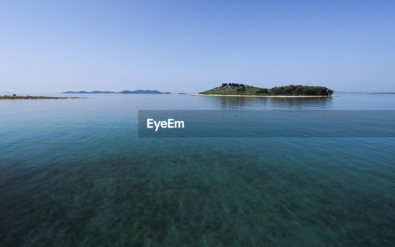 water, beauty in nature, scenics - nature, tranquility, tranquil scene, waterfront, sea, sky, no people, nature, idyllic, day, tree, clear sky, plant, copy space, blue, non-urban scene, outdoors, turquoise colored, shallow