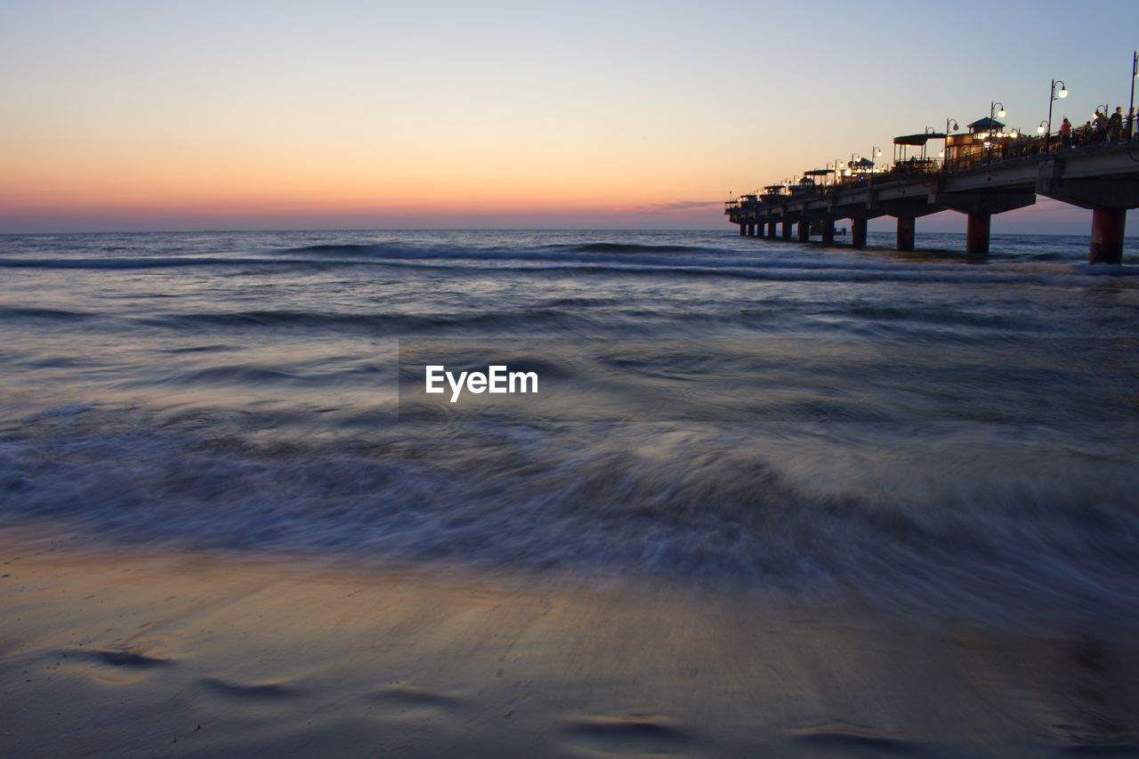 water, sea, sky, sunset, horizon, horizon over water, scenics - nature, beauty in nature, beach, wave, motion, nature, orange color, land, surfing, waterfront, tranquil scene, built structure, outdoors