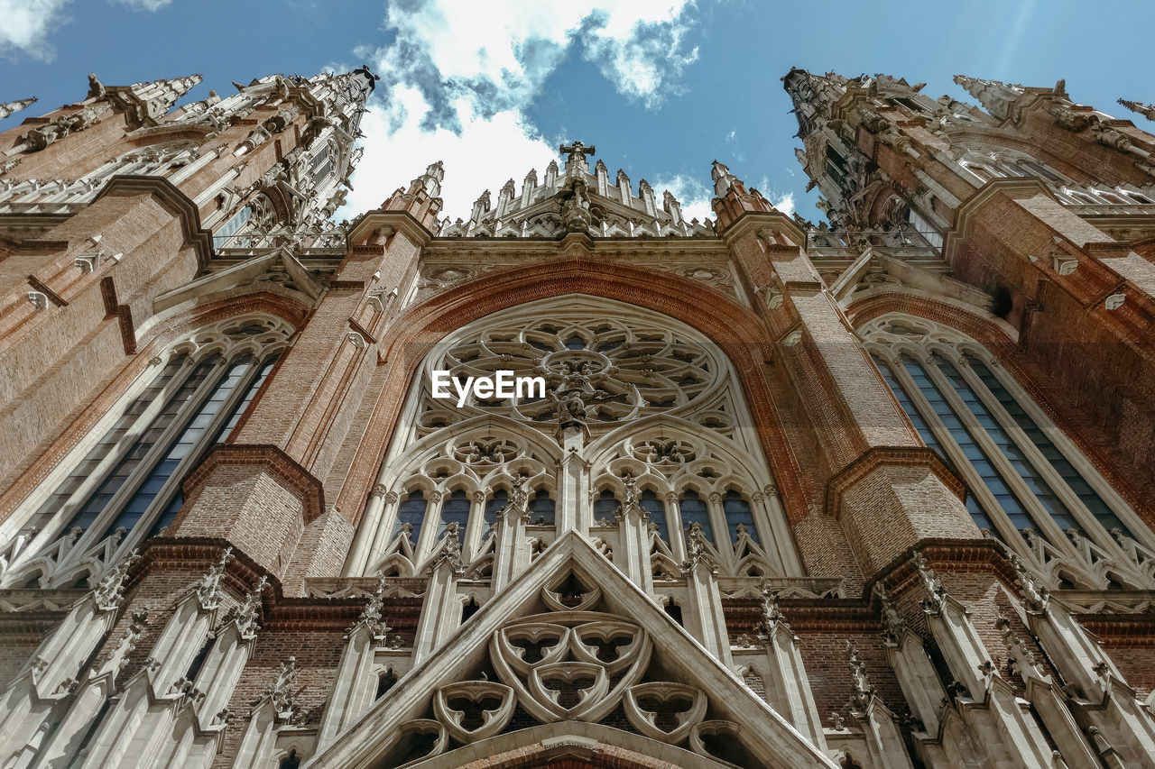 religion, place of worship, spirituality, low angle view, belief, architecture, built structure, building exterior, building, travel destinations, sky, no people, the past, day, history, facade, outdoors, gothic style, ornate, carving