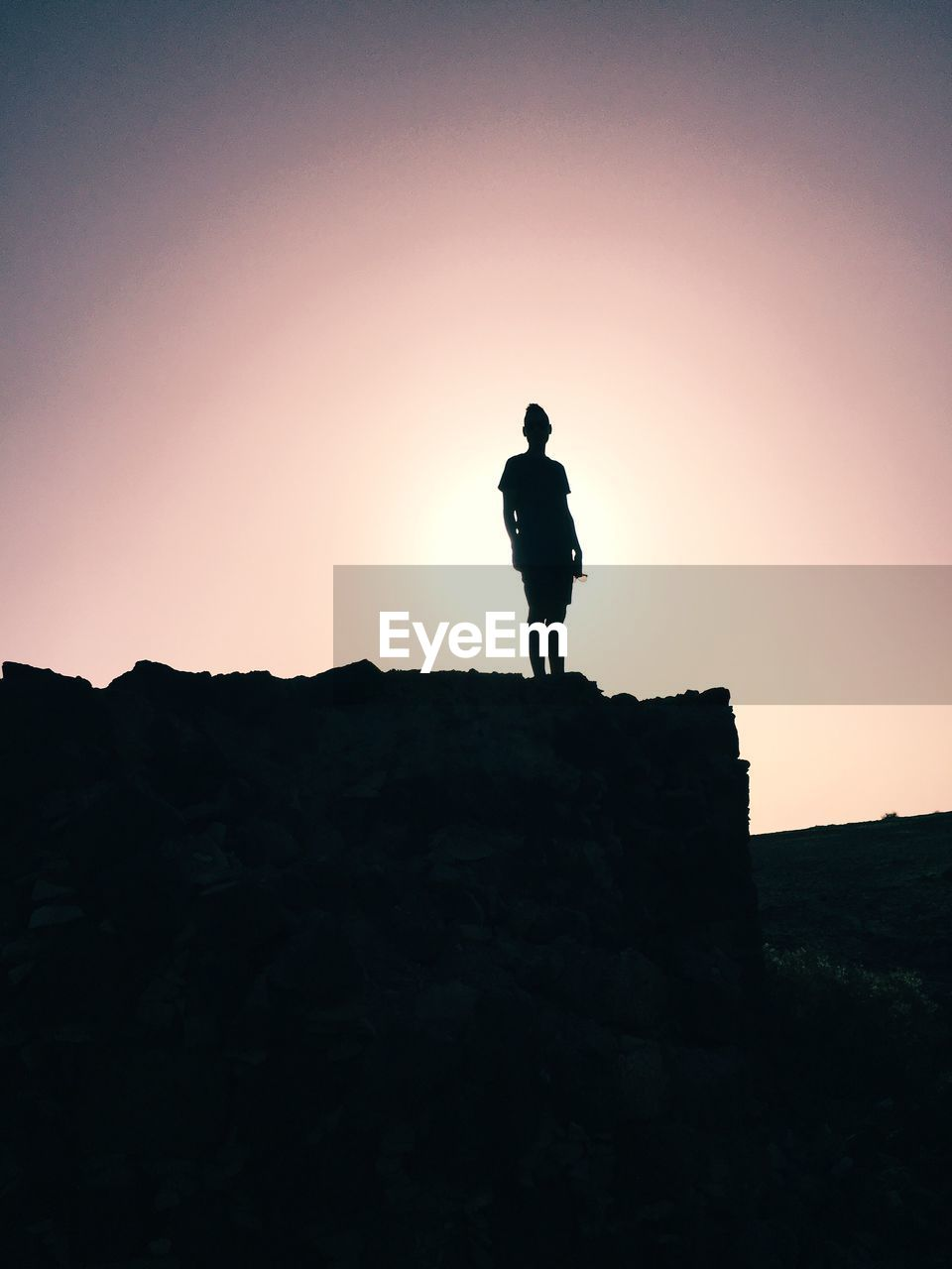 silhouette, sunset, rock - object, hiking, adventure, full length, one person, cliff, nature, standing, landscape, sky, outdoors, clear sky, real people, mountain, men, beauty in nature, climbing, day, one man only, people