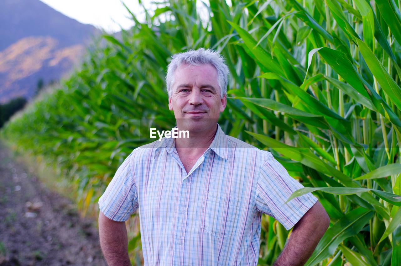 Portrait Of Smiling Mature Farmer Standing Against Plants
