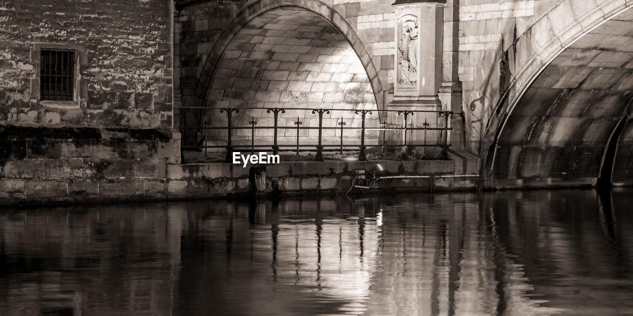 Footpath by river below bridge