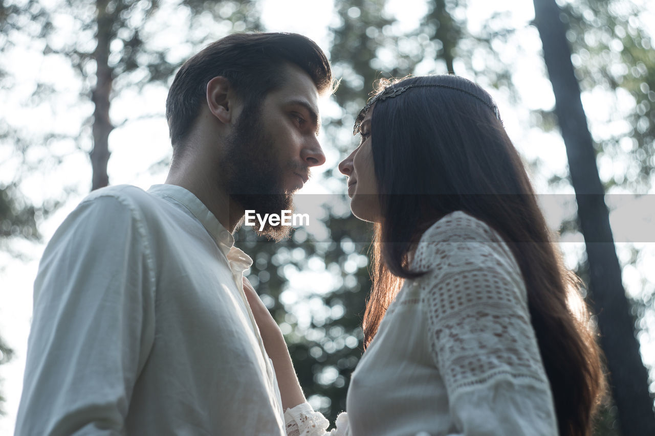 two people, tree, togetherness, real people, young adult, lifestyles, emotion, love, women, young women, young men, adult, focus on foreground, bonding, leisure activity, couple - relationship, casual clothing, side view, day, positive emotion, outdoors, hairstyle