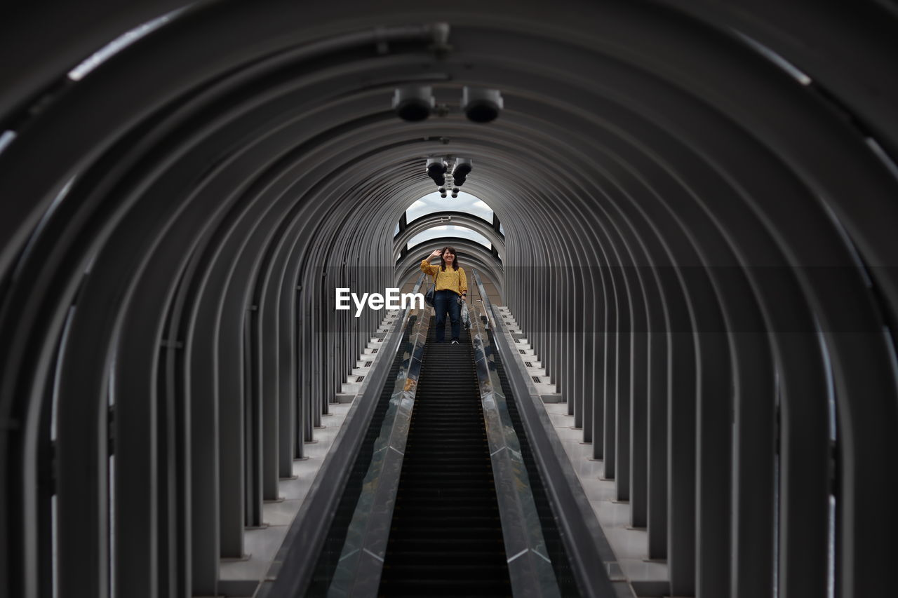 architecture, indoors, the way forward, direction, arch, transportation, diminishing perspective, illuminated, built structure, real people, railing, tunnel, lighting equipment, convenience, steps and staircases, metal, rear view, technology, lifestyles, ceiling