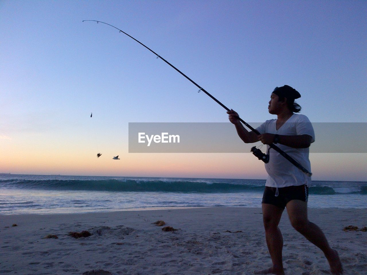 sky, water, sea, beach, land, leisure activity, real people, one person, beauty in nature, holding, rod, fishing rod, scenics - nature, lifestyles, horizon over water, fishing, horizon, activity, men, outdoors